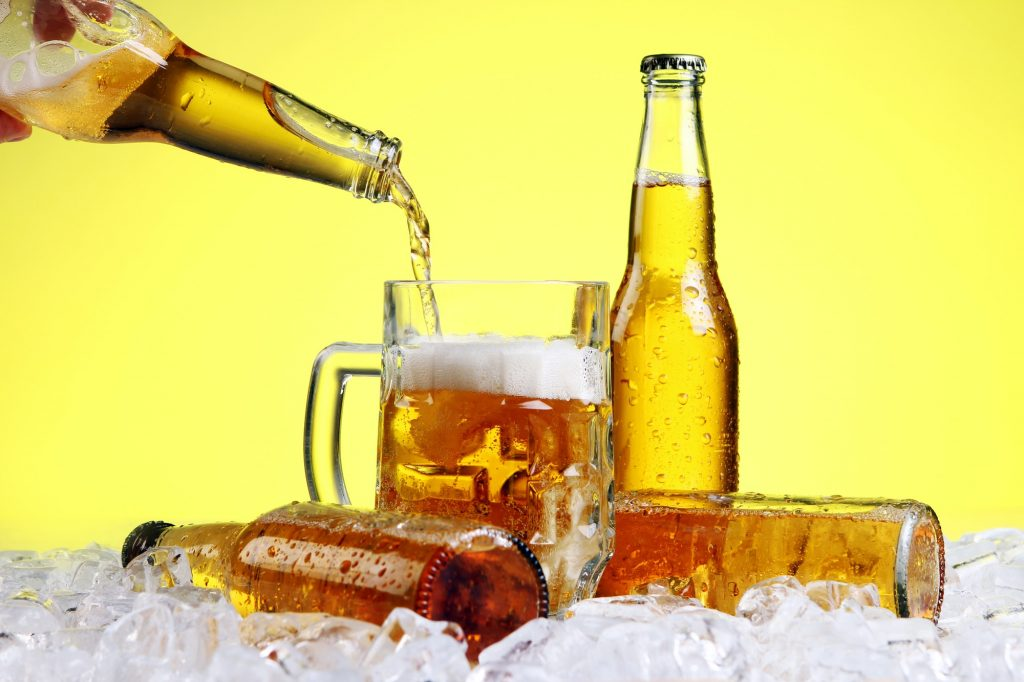 Beer is pouring into glass and beer bottles on ice